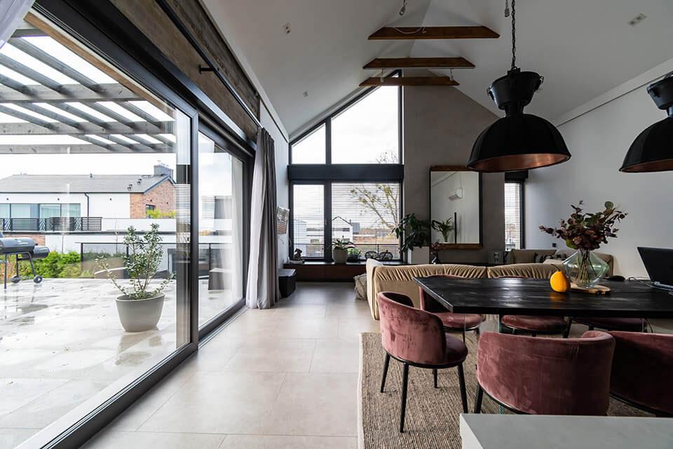 Okno trapezowe w domu stylizowanym na nowoczesną stodołę.
