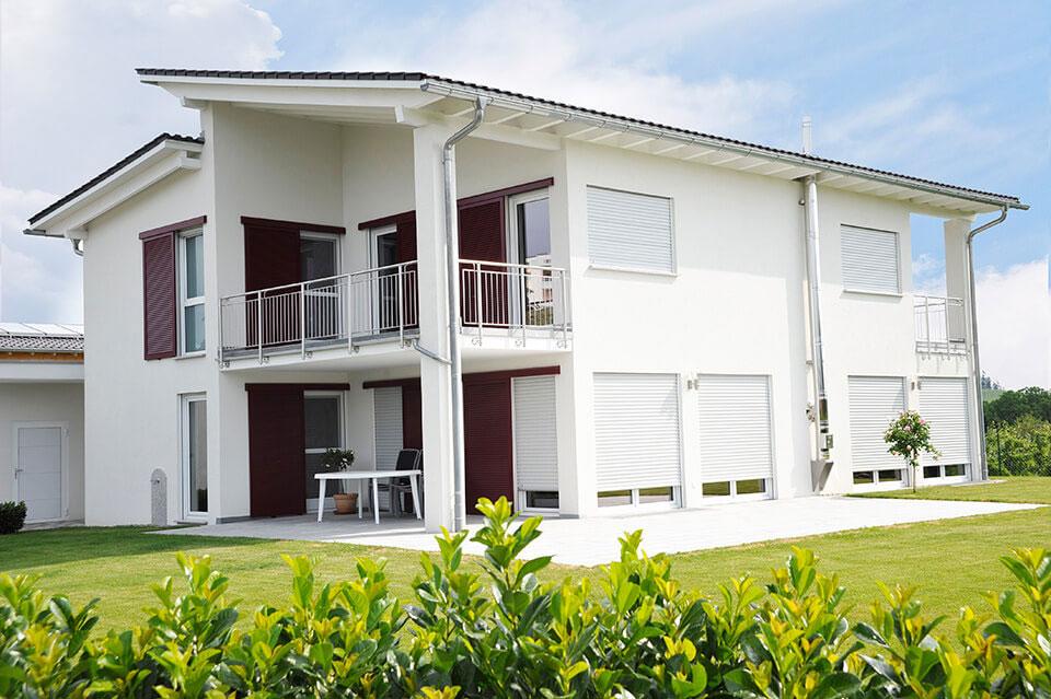 Dom jednorodzinny z białymi oknami i roletami.