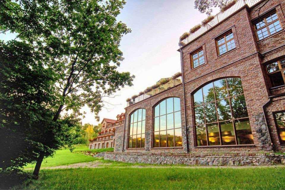 Budynek z czerwonej cegły w stylu industrialnym z dużymi szklanymi witrynami.